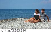 Купить «Счастливые мужчина и женщина сидят за ноутбуком на галечном пляже на берегу моря», видеоролик № 3563316, снято 25 января 2010 г. (c) Losevsky Pavel / Фотобанк Лори