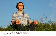 Купить «Молодой человек сидит на траве в парке и слушает музыку в наушниках», видеоролик № 3563500, снято 19 января 2010 г. (c) Losevsky Pavel / Фотобанк Лори