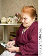 Пожилая женщина с таблетками и рублями на кухне. Стоковое фото, фотограф Светлана Кузнецова / Фотобанк Лори