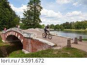 Купить «Велосипедист съезжает с Горбатого мостика в парке-усадьбе Кузьминки-Люблино», эксклюзивное фото № 3591672, снято 27 мая 2012 г. (c) Родион Власов / Фотобанк Лори