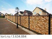 Купить «Забор из декоративного камня и новые двухэтажные коттеджи», фото № 3634884, снято 14 августа 2010 г. (c) Losevsky Pavel / Фотобанк Лори