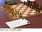 Купить «Деревянные шахматы на шахматной доске. Рядом электронные часы и бумага для записи ходов», фото № 3635560, снято 14 ноября 2010 г. (c) Losevsky Pavel / Фотобанк Лори