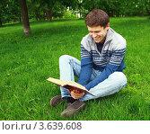 Счастливый молодой мужчина читает книгу и смеется. Стоковое фото, фотограф Оленька Винник / Фотобанк Лори