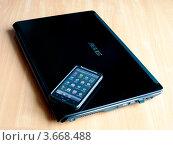 Ноутбук и коммуникатор  лежат на столе (2012 год). Редакционное фото, фотограф OV1957 / Фотобанк Лори