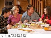 Пара с двумя детьми ужинают в деревянном домике. Стоковое фото, фотограф Monkey Business Images / Фотобанк Лори