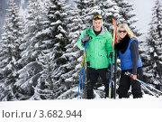 Парень и девушка с лыжами на фоне леса. Стоковое фото, фотограф Monkey Business Images / Фотобанк Лори