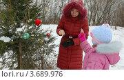 Купить «Мама с дочкой наряжают новогоднюю ель на улице», видеоролик № 3689976, снято 26 мая 2010 г. (c) Losevsky Pavel / Фотобанк Лори