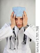 Купить «Молодой врач со стетоскопом в спецодежде на сером фоне», фото № 3701768, снято 22 июля 2012 г. (c) Gagara / Фотобанк Лори