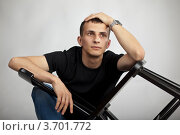 Купить «Серьезный молодой человек сидит со стулом в руках», фото № 3701772, снято 22 июля 2012 г. (c) Gagara / Фотобанк Лори
