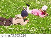 Маленькие мальчик и девочка с мобильными телефонами лежат на зеленой траве в весеннем солнечном парке. Стоковое фото, фотограф Константин Примачук / Фотобанк Лори