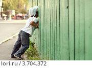 Любопытный мальчик подглядывает сквозь дыру в заборе. Стоковое фото, фотограф Денис Омельченко / Фотобанк Лори