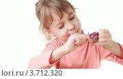 Купить «Девочка пытается убрать обертку с леденца», видеоролик № 3712320, снято 12 декабря 2010 г. (c) Losevsky Pavel / Фотобанк Лори