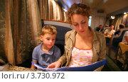 Купить «Мама с сыном рассматривают меню в вагоне-ресторане поезда», видеоролик № 3730972, снято 9 апреля 2011 г. (c) Losevsky Pavel / Фотобанк Лори