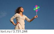 Купить «Женщина стоит на фоне неба  и держит в руках игрушку ветряную мельницу», видеоролик № 3731244, снято 22 марта 2011 г. (c) Losevsky Pavel / Фотобанк Лори