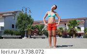 Молодая женщина разминает шею, стоя на песке на фоне отеля. Стоковое видео, видеограф Losevsky Pavel / Фотобанк Лори