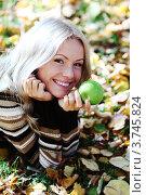 Купить «Женщина с зеленым яблоком лежит на опавших листьях», фото № 3745824, снято 1 октября 2010 г. (c) Иван Михайлов / Фотобанк Лори