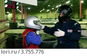 Купить «Тренер по картингу помогает маленькому мальчику надеть шлем», видеоролик № 3755776, снято 10 сентября 2011 г. (c) Losevsky Pavel / Фотобанк Лори