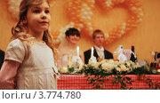 Купить «Маленькая девочка на свадьбе стоит на фоне праздничного стола и жениха с невестой», видеоролик № 3774780, снято 26 декабря 2011 г. (c) Losevsky Pavel / Фотобанк Лори
