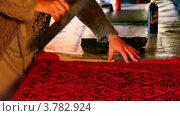 Женщина нажимает на печатную форму и делает орнамент на ткани на столе. Стоковое видео, видеограф Losevsky Pavel / Фотобанк Лори