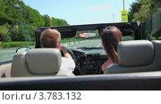Купить «Молодой человек и девушка едут  в кабриолете по городу и улыбаются летним днем», видеоролик № 3783132, снято 26 апреля 2012 г. (c) Losevsky Pavel / Фотобанк Лори