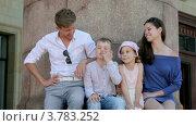 Купить «Молодой человек и девушка с маленьким мальчиком и девочкой сидят у колонн летним днем», видеоролик № 3783252, снято 26 апреля 2012 г. (c) Losevsky Pavel / Фотобанк Лори