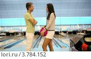 Купить «Парень с девушкой говорит и улыбается возле боулинга в клубе», видеоролик № 3784152, снято 7 апреля 2012 г. (c) Losevsky Pavel / Фотобанк Лори