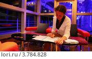 Купить «Женщина держит ручку и читает документы, сидя за столом в зале», видеоролик № 3784828, снято 21 июня 2012 г. (c) Losevsky Pavel / Фотобанк Лори