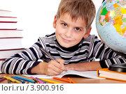 Мальчик занимается уроками за столом. Рядом книги и глобус. Стоковое фото, фотограф Сергей Фигурный / Фотобанк Лори