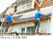 Купить «Два строителя ремонтируют крышу коттеджа», фото № 3936560, снято 22 июня 2012 г. (c) Дмитрий Калиновский / Фотобанк Лори