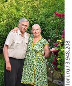 Пожилая пара весной у цветника с розами и гортензией на фоне плодовых деревьев. Стоковое фото, фотограф Анна Мартынова / Фотобанк Лори