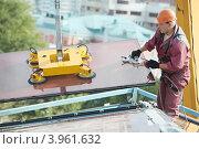 Купить «Рабочий устанавливает стекло на фасад  здания», фото № 3961632, снято 18 сентября 2012 г. (c) Дмитрий Калиновский / Фотобанк Лори