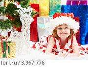 Купить «Веселая девочка в новогоднем колпаке лежит на фоне подарков около оленя», фото № 3967776, снято 23 декабря 2011 г. (c) Дмитрий Калиновский / Фотобанк Лори