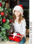 Купить «Симпатичная девочка с подарком в колпаке Санта Клауса сидит около новогодней елки», фото № 3988332, снято 4 ноября 2012 г. (c) Оксана Гильман / Фотобанк Лори