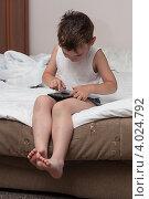 Купить «Неодетый ребёнок сидя на кровати играет в игры на смартфоне», эксклюзивное фото № 4024792, снято 15 июля 2012 г. (c) Родион Власов / Фотобанк Лори