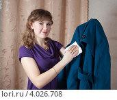 Купить «Симпатичная кудрявая девушка чистит салфеткой пальто», фото № 4026708, снято 18 февраля 2012 г. (c) Яков Филимонов / Фотобанк Лори
