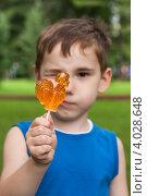 Купить «Мальчик смотрит одним глазом на леденец на палочке», эксклюзивное фото № 4028648, снято 13 июля 2012 г. (c) Родион Власов / Фотобанк Лори