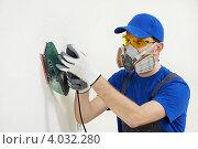 Купить «Строитель в защитной маске выравнивает стену с помощью шлифовальной машины», фото № 4032280, снято 16 ноября 2012 г. (c) Дмитрий Калиновский / Фотобанк Лори