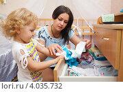 Купить «Молодая мама с дочкой убирают вещи в комод. Фокус на женщине.», фото № 4035732, снято 4 ноября 2012 г. (c) Владимир Мельников / Фотобанк Лори