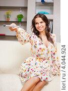 Молодая женщина сидит на диване с пультом дистанционного управления от телевизора в руках. Стоковое фото, фотограф Syda Productions / Фотобанк Лори