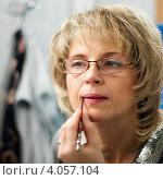 Купить «Ухоженная женщина средних лет подводит губы контурным карандашом перед зеркалом», эксклюзивное фото № 4057104, снято 23 ноября 2012 г. (c) Игорь Низов / Фотобанк Лори