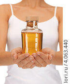 Купить «Женская стройная фигура с бутылкой ароматического масла в руках на белом фоне», фото № 4063440, снято 16 сентября 2012 г. (c) Syda Productions / Фотобанк Лори