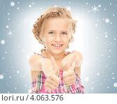 Купить «Маленькая светловолосая девочка в сарафане с поднятыми большими пальцами на руках вверх на сером фоне со снежинками», фото № 4063576, снято 28 августа 2010 г. (c) Syda Productions / Фотобанк Лори