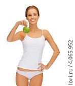 Купить «Стройная молодая женщина с зеленым яблоком в руке», фото № 4065952, снято 16 сентября 2012 г. (c) Syda Productions / Фотобанк Лори