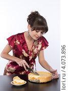 Купить «Молодая девушка в домашнем халате отрезает кусок домашнего торта», фото № 4073896, снято 1 декабря 2012 г. (c) Михаил Иванов / Фотобанк Лори