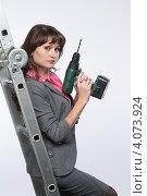Купить «Девушка в деловом костюме с электро дрелью в руке», фото № 4073924, снято 1 декабря 2012 г. (c) Михаил Иванов / Фотобанк Лори