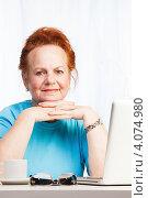 Пожилая рыжеволосая женщина за столом с ноутбуком. Стоковое фото, фотограф Сергей Новиков / Фотобанк Лори