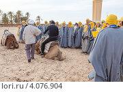 Экскурсовод показывает туристам, как правильно слезать с верблюда. Douz, Tunisia (2012 год). Редакционное фото, фотограф Кекяляйнен Андрей / Фотобанк Лори