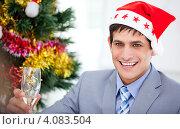 Купить «Весёлый мужчина в костюме и шапочке Санта Клауса с бокалом шампанского перед ёлкой», фото № 4083504, снято 29 февраля 2020 г. (c) Wavebreak Media / Фотобанк Лори
