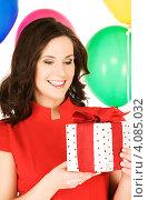 Купить «Привлекательная молодая женщина с длинными темными волосами с разноцветными воздушными шарами и подарком в руках на белом фоне», фото № 4085032, снято 19 сентября 2009 г. (c) Syda Productions / Фотобанк Лори