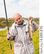 Купить «Мужчина с пойманной щукой и удочкой в руках на фоне реки», эксклюзивное фото № 4089876, снято 2 октября 2012 г. (c) Игорь Низов / Фотобанк Лори